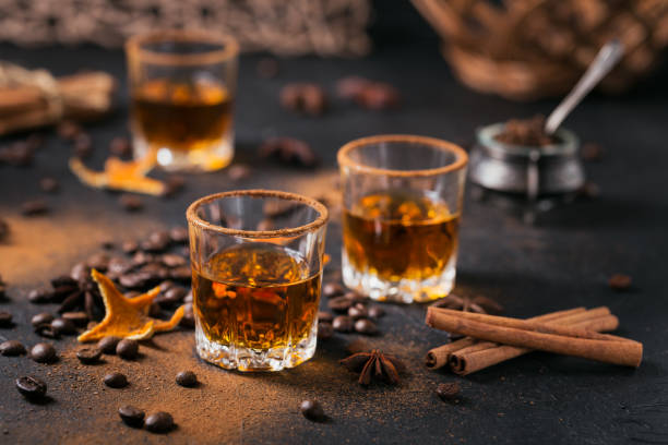 Whiskey, brandy or liquor, spices, anise stars, coffee beans, cinnamon sticks Whiskey, brandy or liquor, coffee beans, spices and decorations on dark background. Seasonal holidays concept. brandy stock pictures, royalty-free photos & images