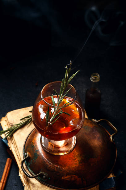 Whiskey cocktail with ice and burnt rosemary. Dark background, vintage papers, dramatic ligting. Vertical composition. Whiskey cocktail with ice and burnt rosemary. Dark background, vintage papers, dramatic ligting. Vertical composition. brandy stock pictures, royalty-free photos & images