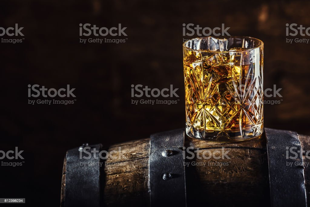 Whiskey drink. Glass of whiskey on old wooden barrel stock photo