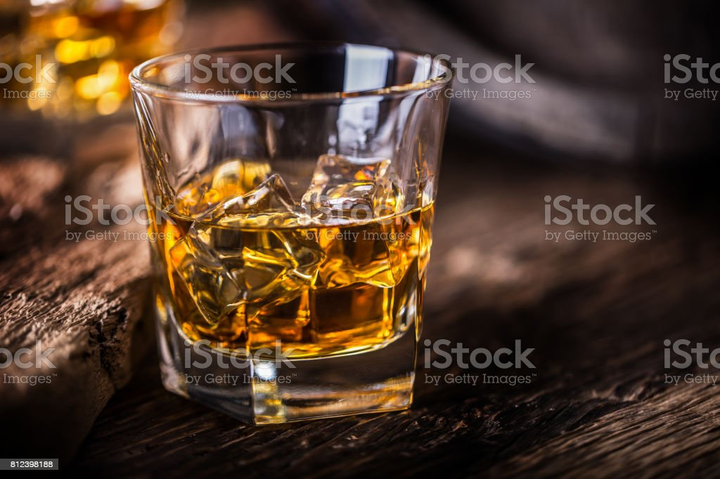 Whiskey drink. Whiskey drinks on rustic oak wood with ice cubes stock photo
