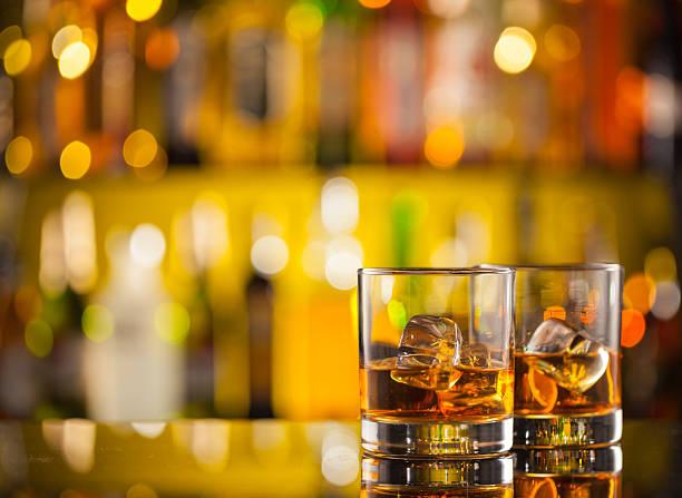 whiskey drinks an der bar - goldene bar stock-fotos und bilder