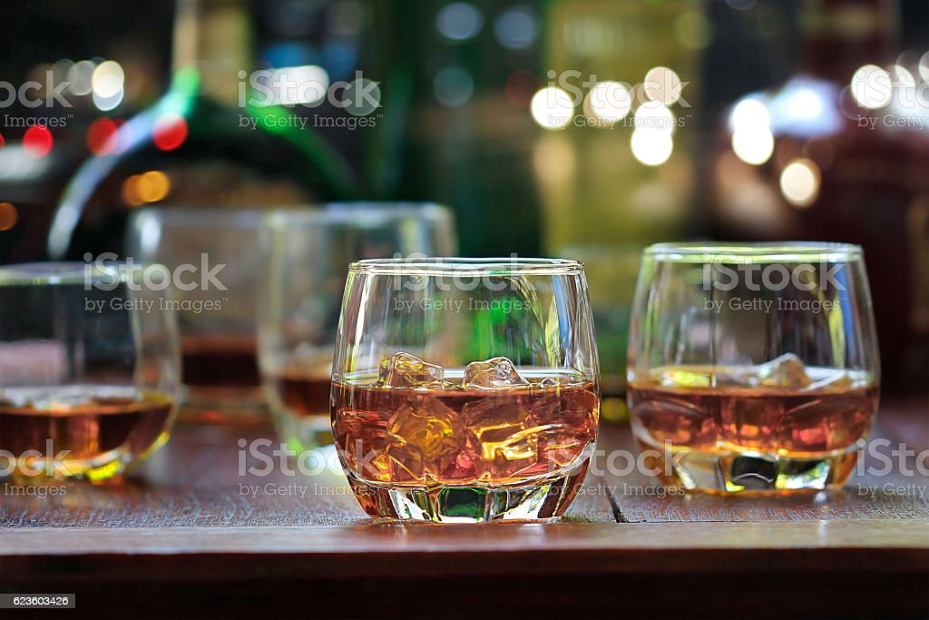 whiskey drinks with ice on wooden background stock photo