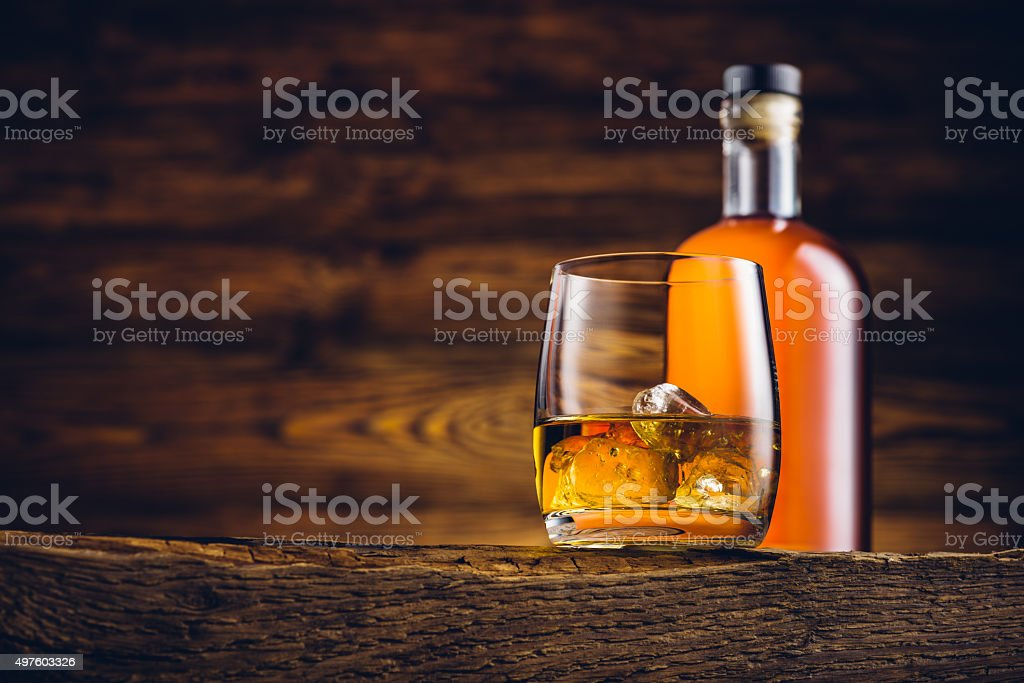 Whiskey glass and bottle on the old wooden table stock photo