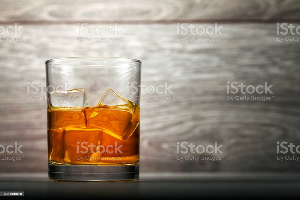 Whiskey glass and ice on wooden background stock photo
