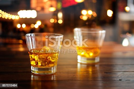 istock Whiskey glass drink with ice cube on wooden table in colorful night bar 857015464