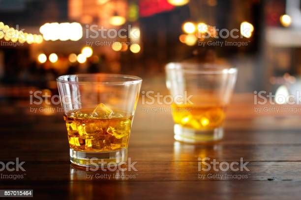 Whiskey glass drink with ice cube on wooden table in colorful night picture id857015464?b=1&k=6&m=857015464&s=612x612&h=c tj7ntmtucbgh8jwsmhx9tmwxlol0o9q5ra8rgzuuy=