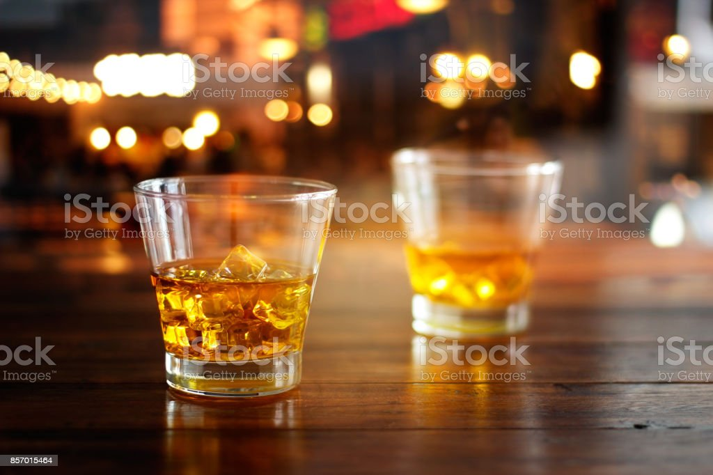 Whiskey glass drink with ice cube on wooden table in colorful night bar stock photo