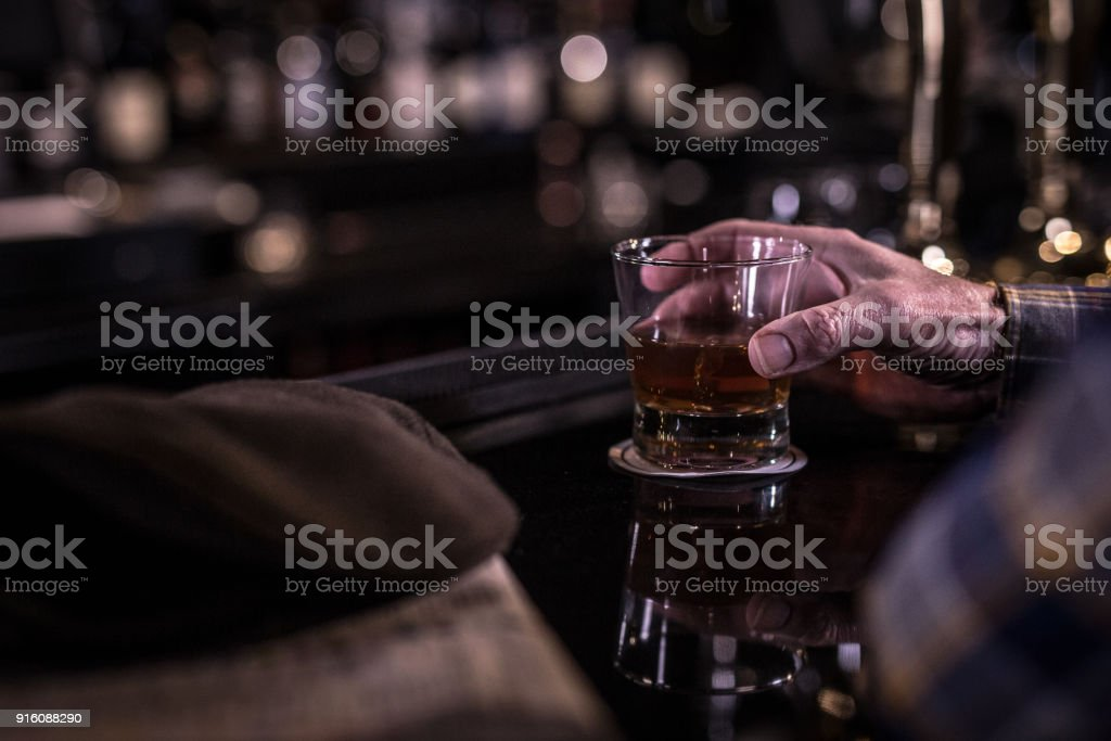 Whiskey glass in hand stock photo