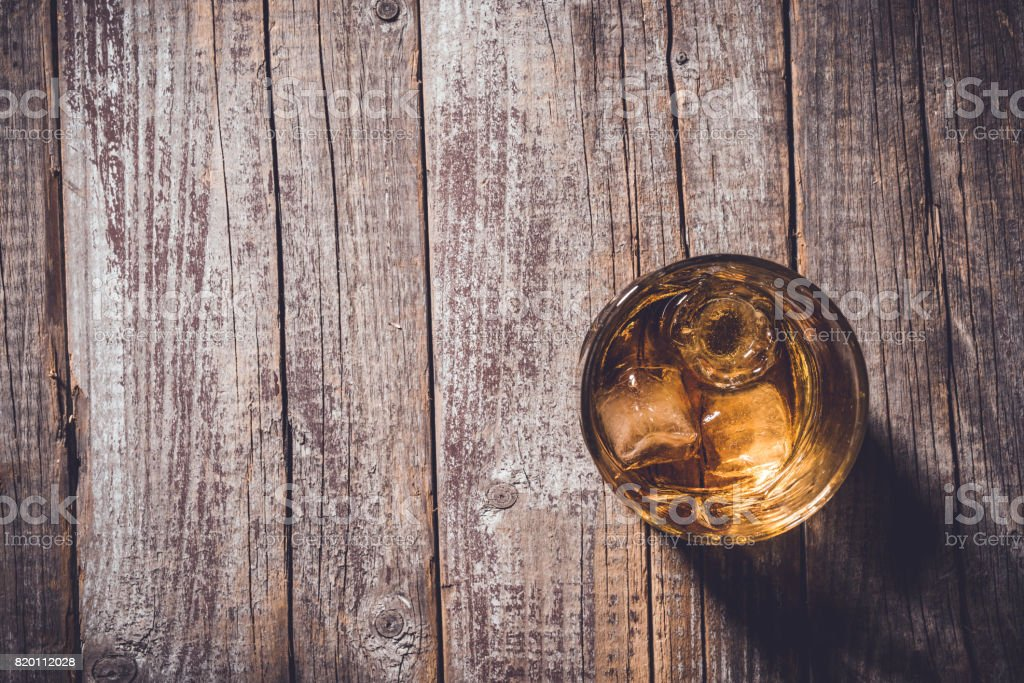 Whiskey glass on an old wooden table. stock photo