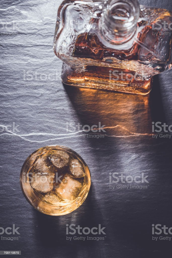 Whiskey glass on dark stone table stock photo
