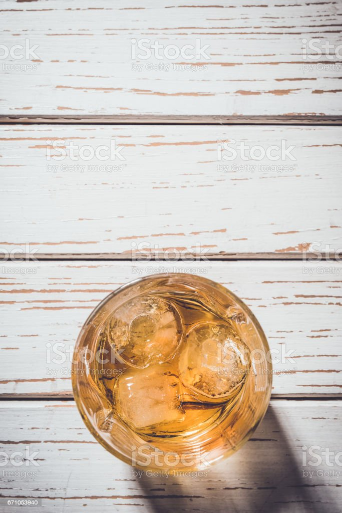Whiskey glass with ice cubes on an old wooden table stock photo