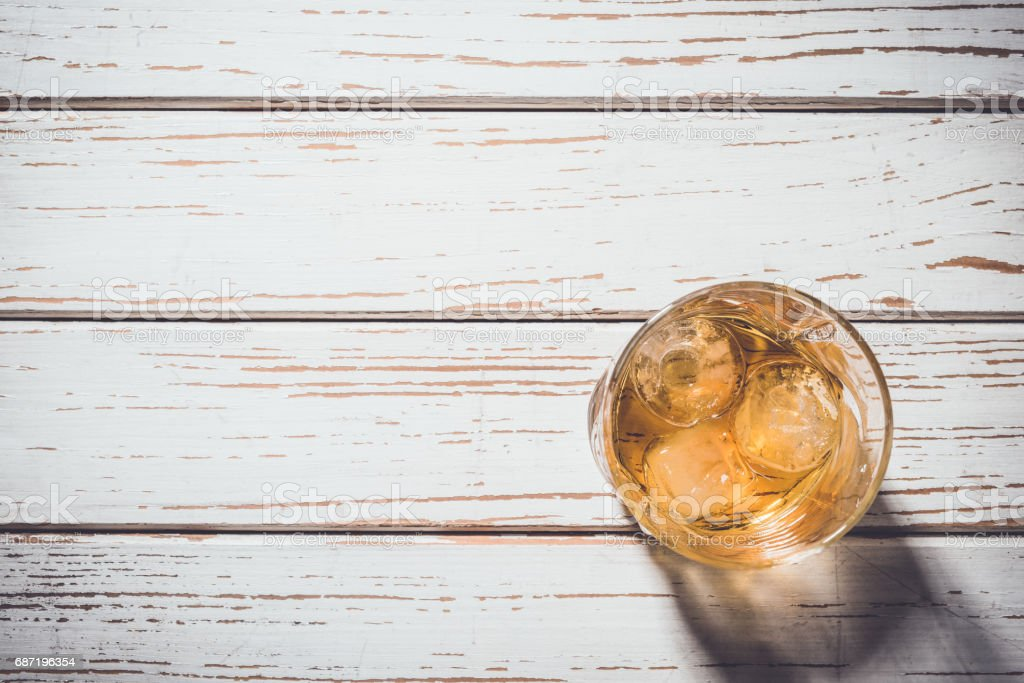 Whiskey glass with ice cubes on white wooden table stock photo