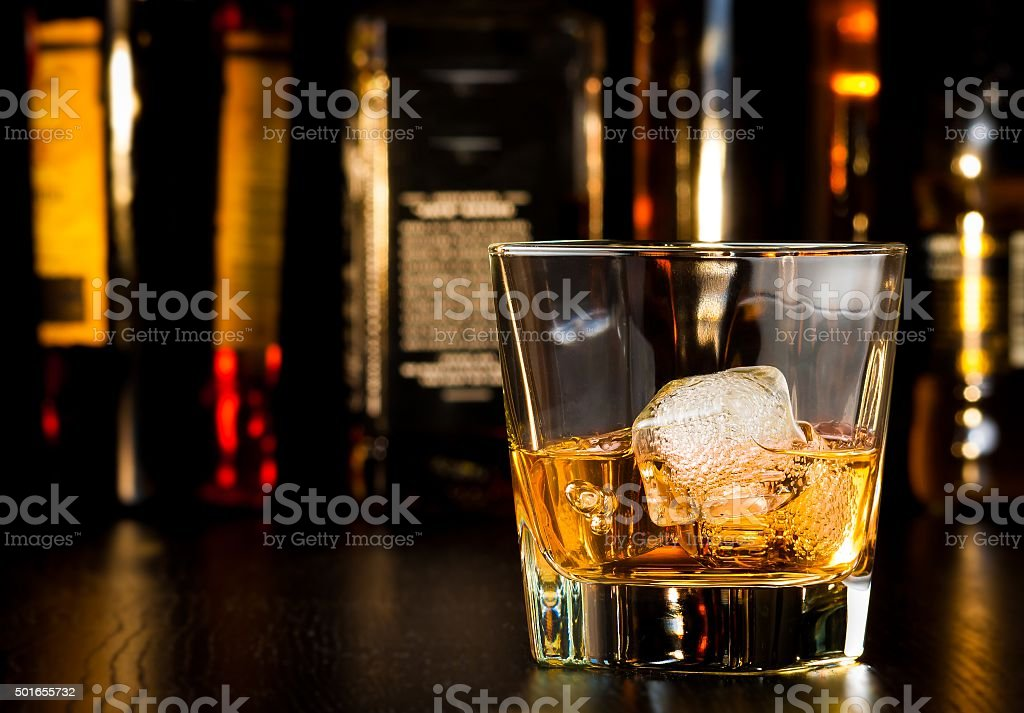 whiskey glass with ice in front of bottles stock photo