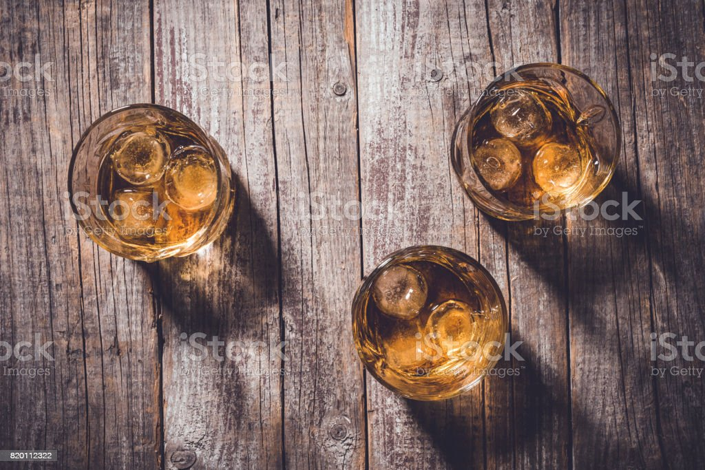 Whiskey glasses on an old wooden table. stock photo