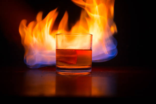 Whiskey in fire concept. Glass of whiskey and ice on wooden surface with color light and fog on background. Close up. stock photo