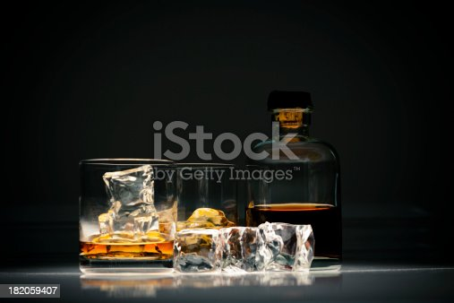 Close-up view of alcoholic beverage on ice in a glass on isolated background.