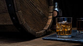 Two glasses and bottle of whiskey on wooden bar counter near oak whiskey barrel. Black background