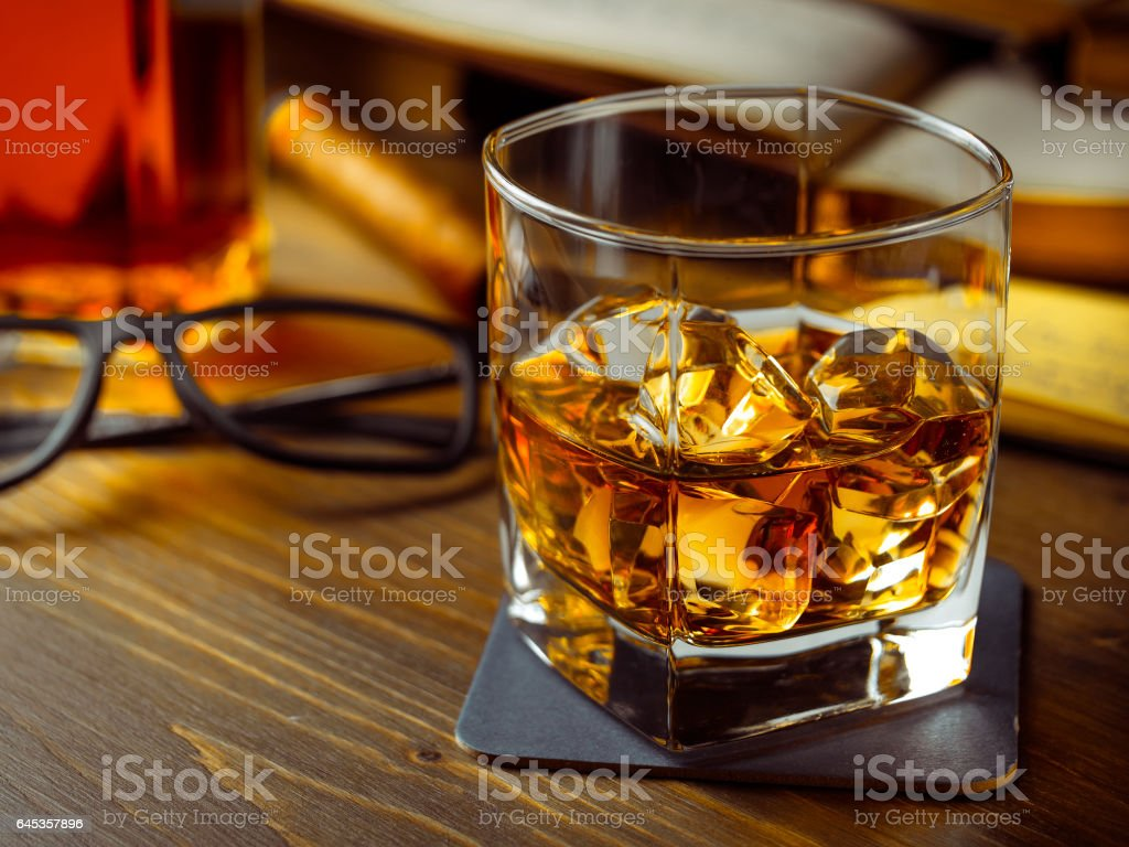 Whiskey on the rocks and scholar books stock photo