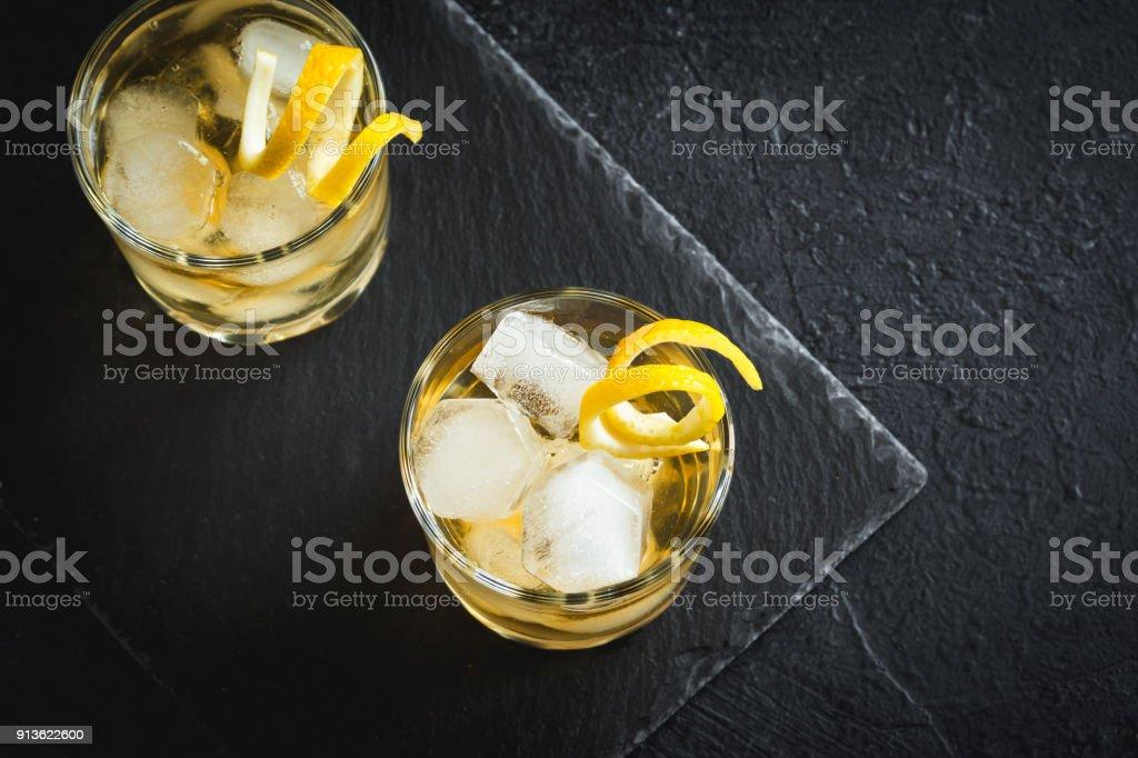 Whiskey on the rocks with lemon peel stock photo