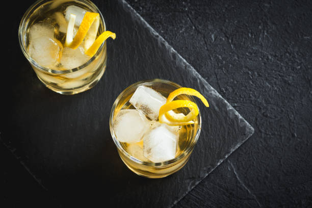 Whiskey on the rocks with lemon peel stock photo