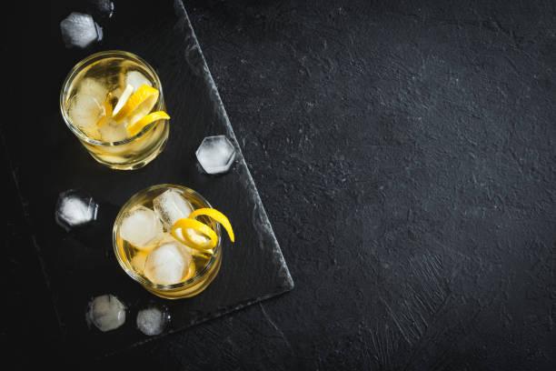 whisky en las rocas con cáscara de limón - cóctel fotografías e imágenes de stock