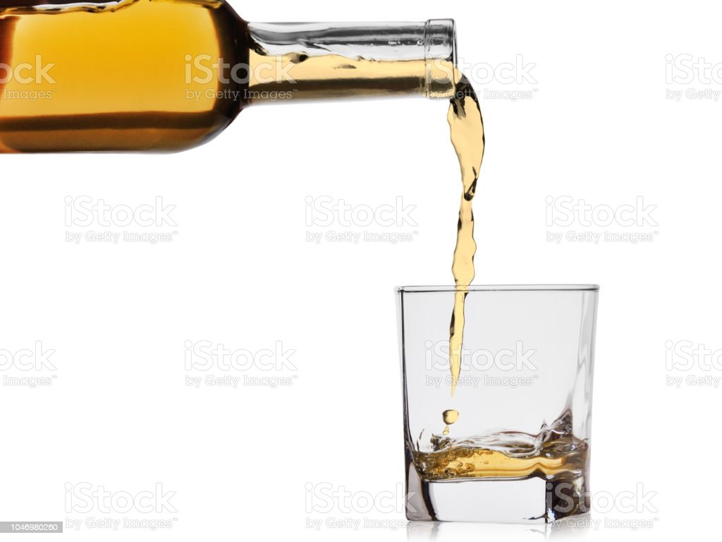 whiskey or cognac poured into a glass from a bottle isolated on a white background stock photo