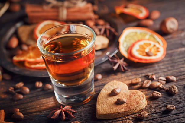 whiskey or liqueur, cookies, spices and decorations on wooden background. - orangenlikör stock-fotos und bilder