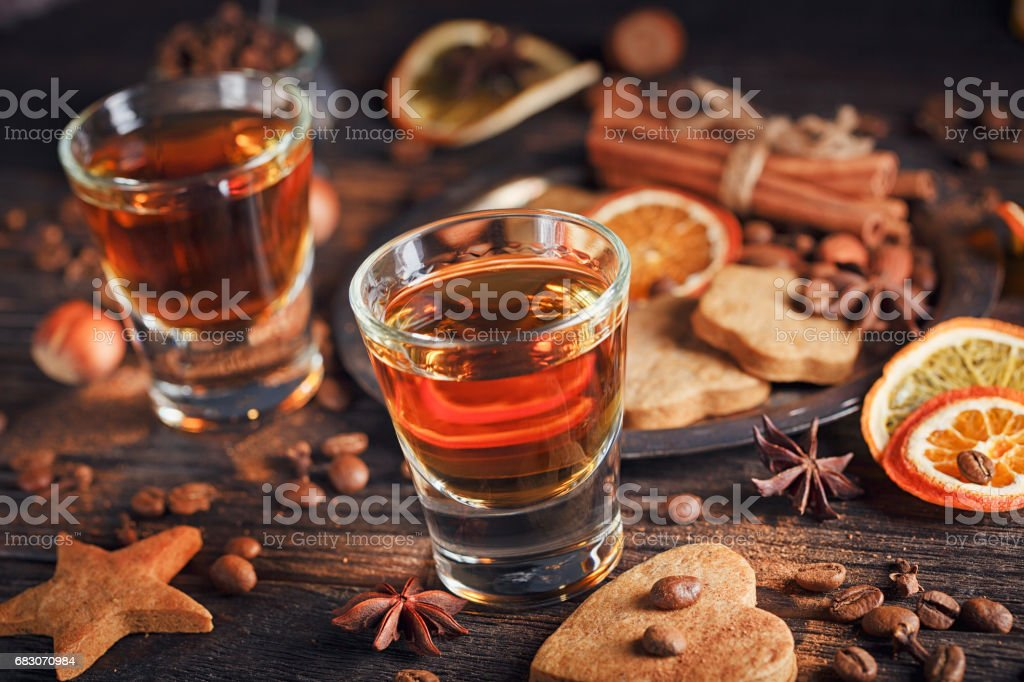Whiskey or liqueur, cookies, spices and decorations on wooden background. foto de stock royalty-free