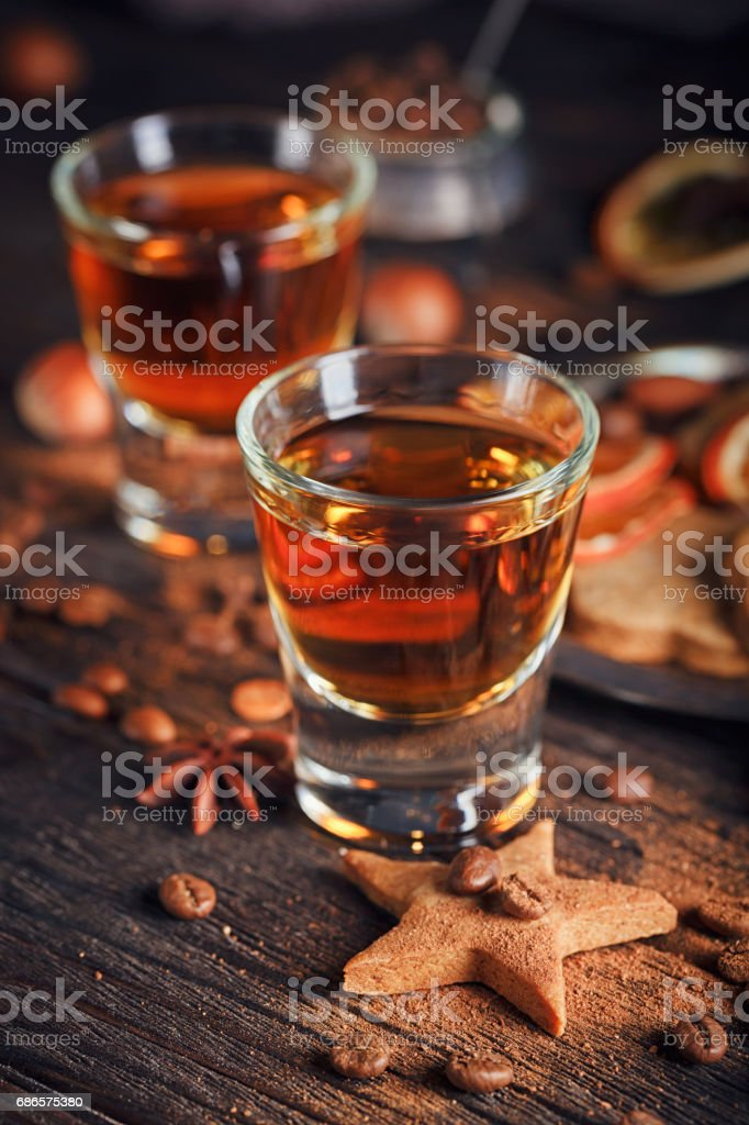 Whiskey or liqueur, cookies, spices and decorations on wooden background. royalty-free stock photo