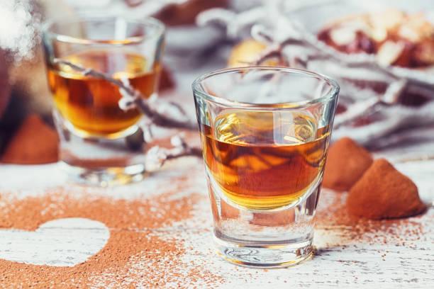 whiskey oder likör, bonbons schokolade trüffel in kakaopulver und weihnachten dekorationen auf weißem hintergrund aus holz. - schokolikör stock-fotos und bilder