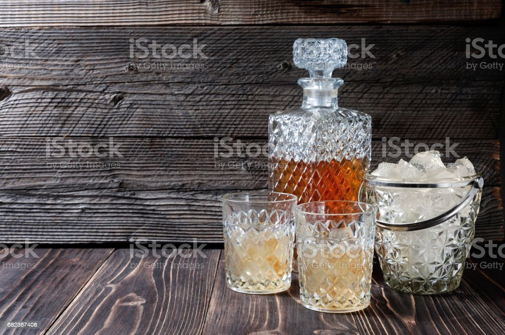 Whiskey or Scotch from carafe into a glass with ice cubes zbiór zdjęć royalty-free