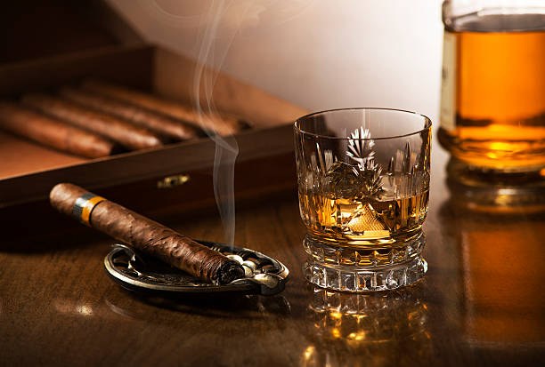 Whiskey Glass of whiskey with ice cubes and smoking cigar on wooden table brandy stock pictures, royalty-free photos & images