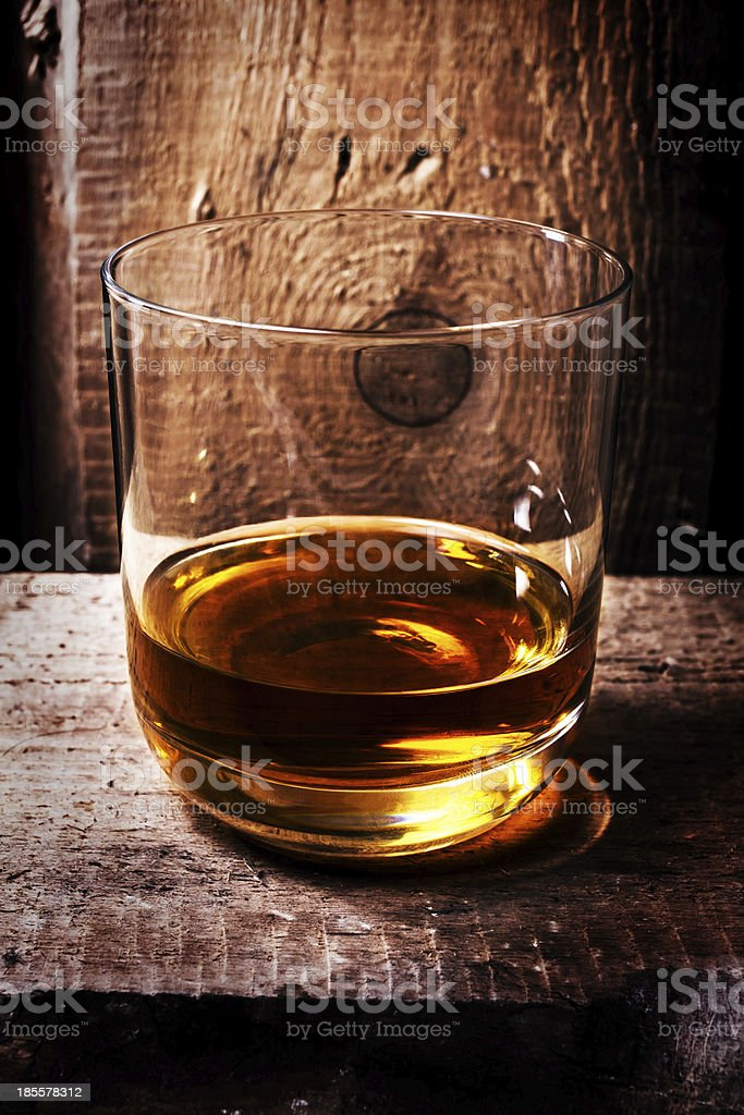 Whiskey Scotch in a glass and  bottle on old wooden stock photo