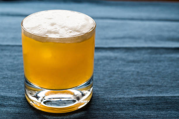whiskey sour cocktail with foam and blue backround. - kwaśny smak zdjęcia i obrazy z banku zdjęć