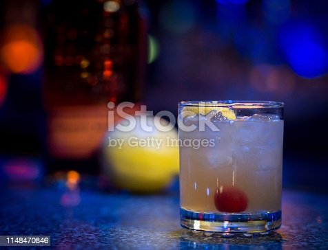 A perfectly made Whiskey Sour on the rocks garnished with a cherry and a lemon twist sits on a bar counter with the ingredients out of focus behind them.