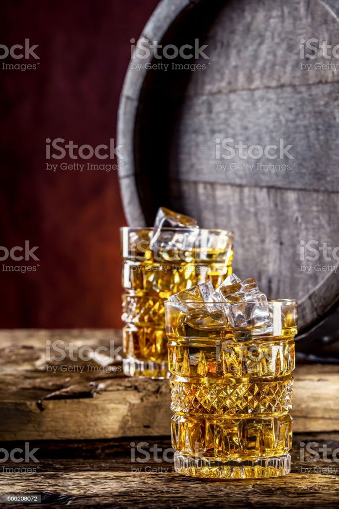 Whiskey. Two cups full of beverage whiskey brandy or cognac with ice cubes in retro style. Old oak barrel in the background stock photo