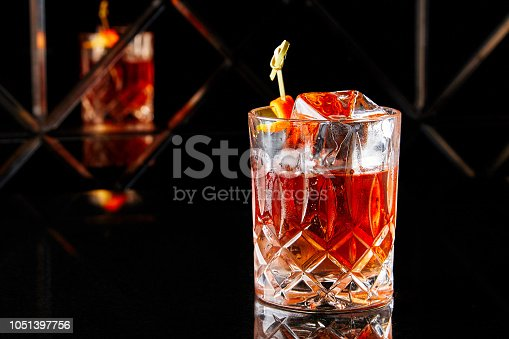 872334598istockphoto Whiskey with a large cube of ice 1051397756