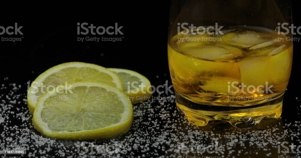 Whiskey with ice cubes in drinking glass on black background. Glass...