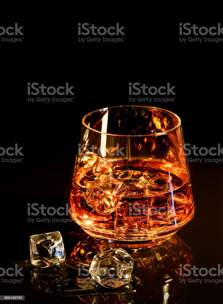 Whiskey with ice in glass on black background stock photo