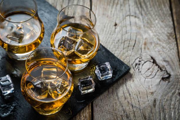 whisky avec glaçons au verre - spiritueux photos et images de collection