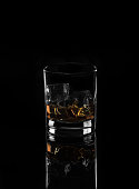 Alcohol.Wwhiskey with ice on a black background