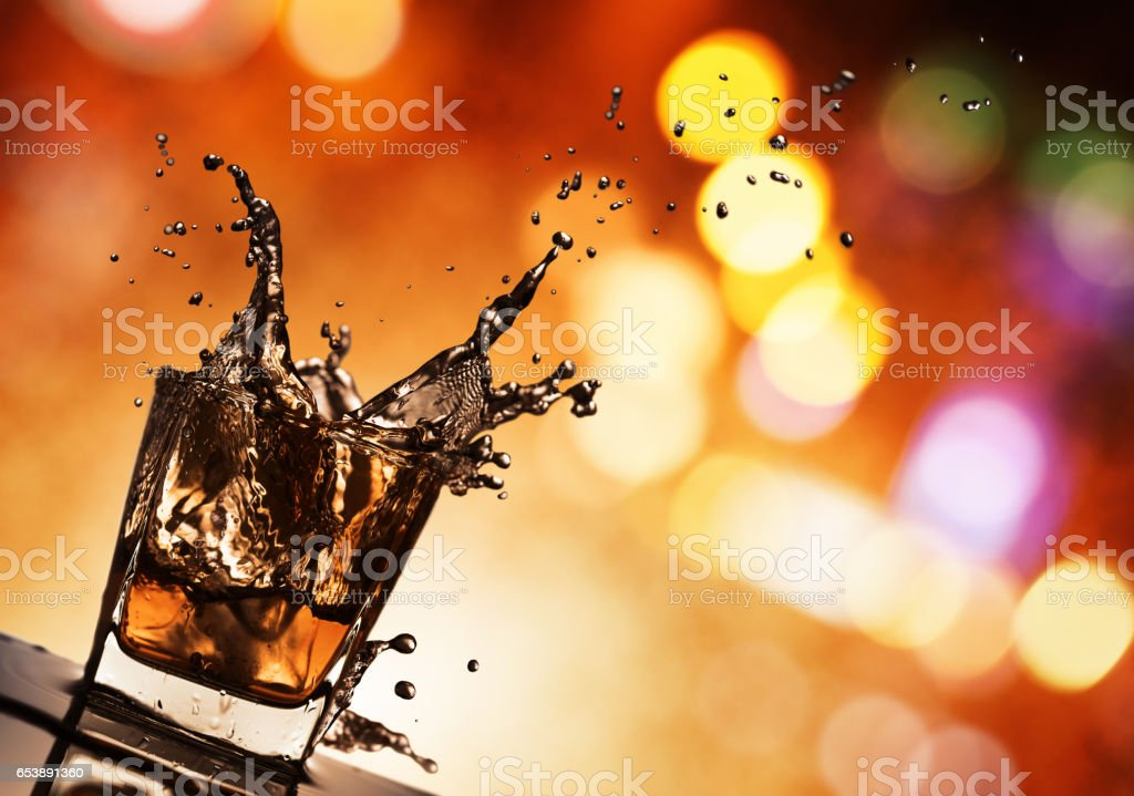 whiskey with ice on a glass table in bar stock photo