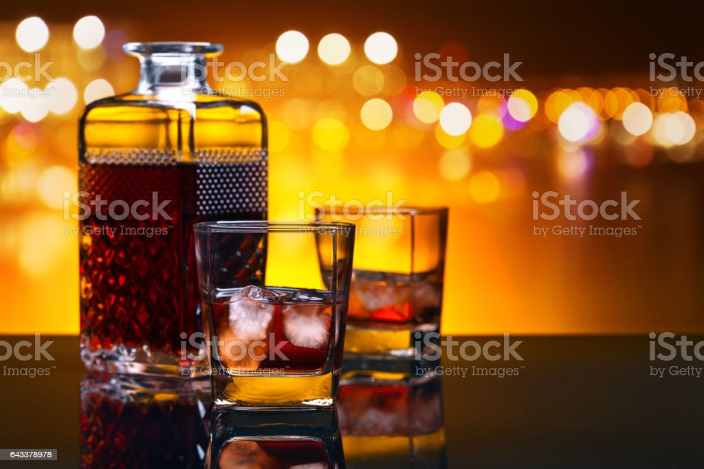 Whiskey with ice on a table in bar stock photo