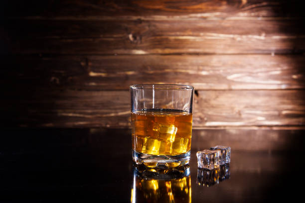 whiskey with ice on a wooden table stock photo