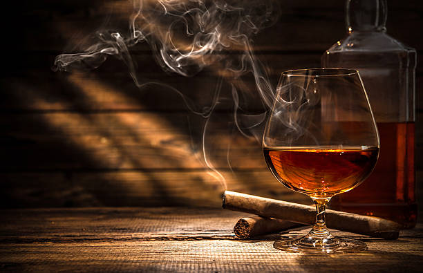 Whiskey with smoking cigar Glass of whiskey with smoking cigar and ice cubes on wooden table brandy stock pictures, royalty-free photos & images