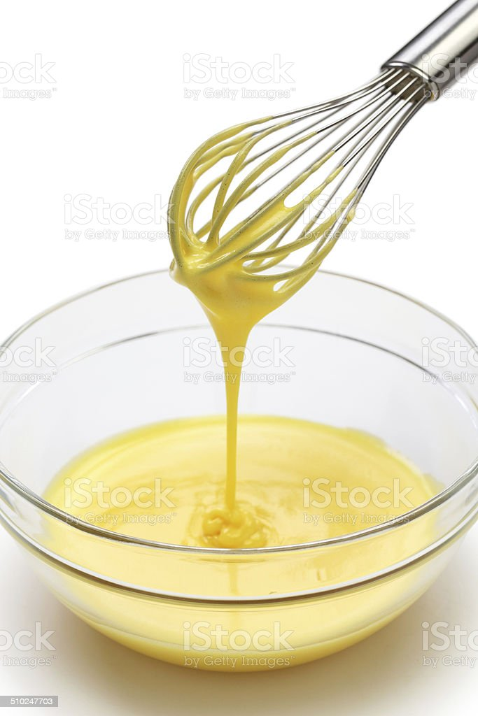 whisking egg yolks and sugar in a bowl stock photo