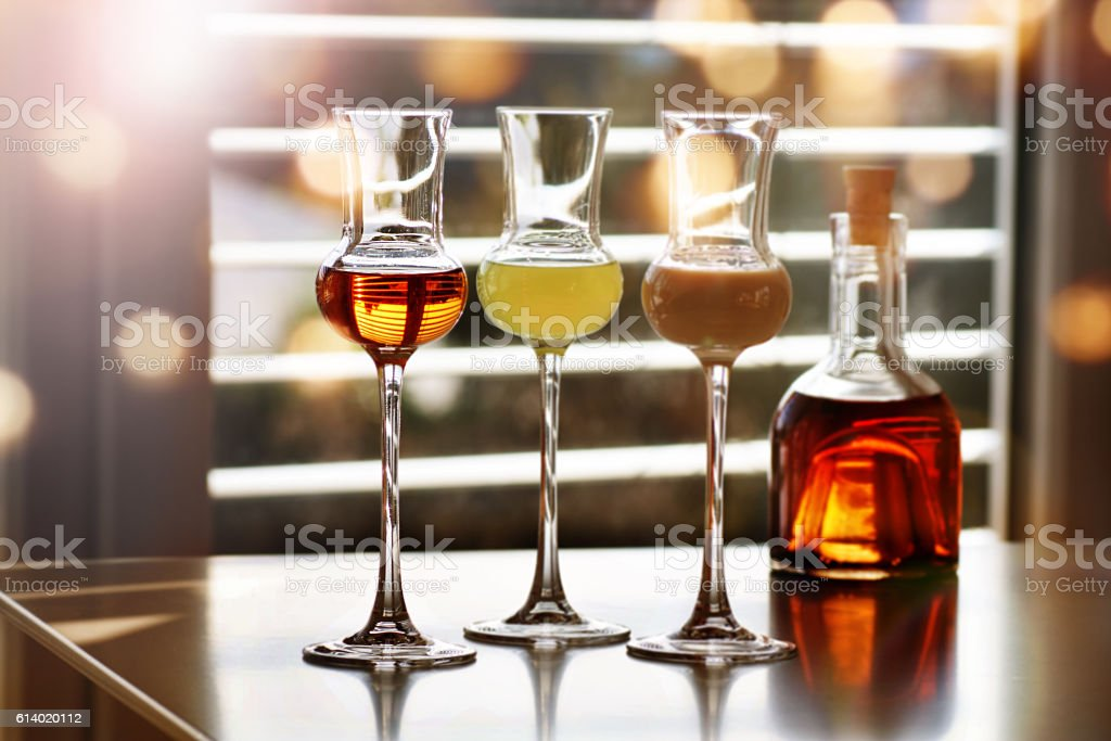 Whisky and liqueur in front of a window stock photo