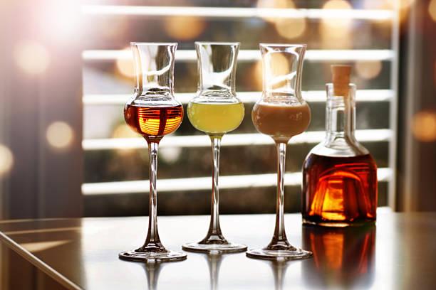 whisky and liqueur in front of a window - dekorierte schnapsflaschen stock-fotos und bilder