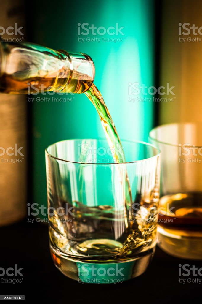 Whisky being poured from clear glass bottle into glass tumbler with Scotch malt whisky bottles in background stock photo
