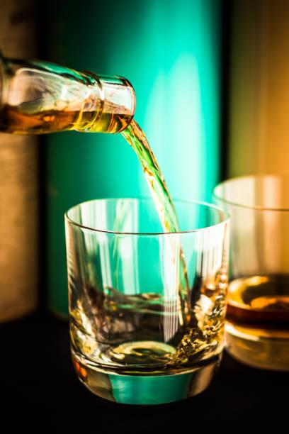whisky aus gegossen wird klar glasflasche in glas becher mit scotch malt whisky-flaschen im hintergrund - goldene bar stock-fotos und bilder